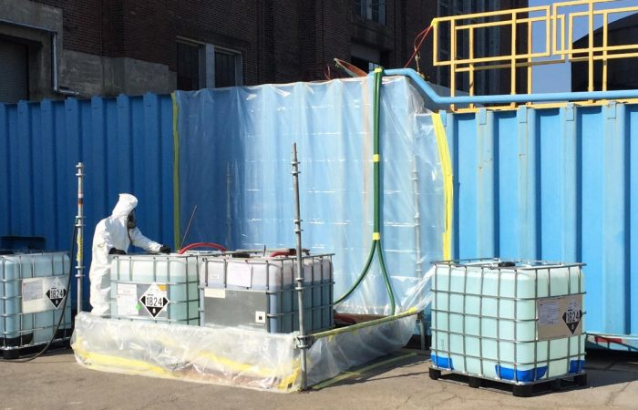 Person in clean suit sorting liquid chemicals